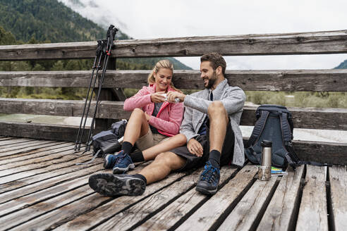 Young couple having a break on a wooden bridge during a hiking trip, Vorderriss, Bavaria, Germany - DIGF08349
