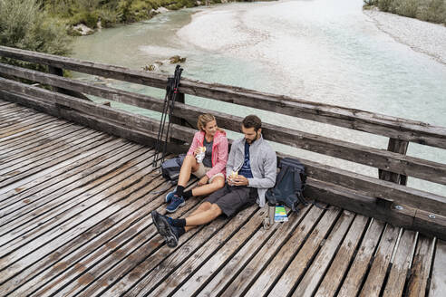 Young couple having a break on a wooden bridge during a hiking trip, Vorderriss, Bavaria, Germany - DIGF08352