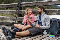 Young couple having a break on a wooden bridge during a hiking trip, Vorderriss, Bavaria, Germany - DIGF08355