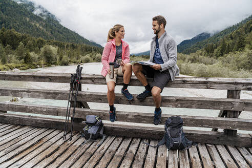 Young couple having a break on a wooden bridge during a hiking trip, Vorderriss, Bavaria, Germany - DIGF08358