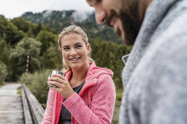 Young woman with drink smiling at man during a hiking trip, Vorderriss, Bavaria, Germany - DIGF08361