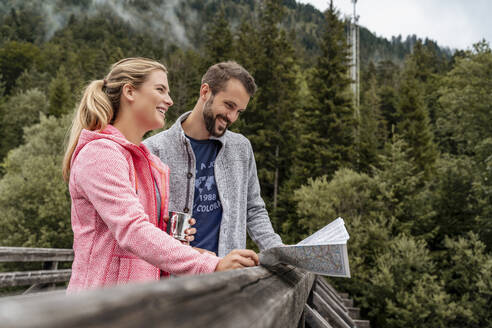Happy young couple on a hiking trip reading map on wooden bridge, Vorderriss, Bavaria, Germany - DIGF08364