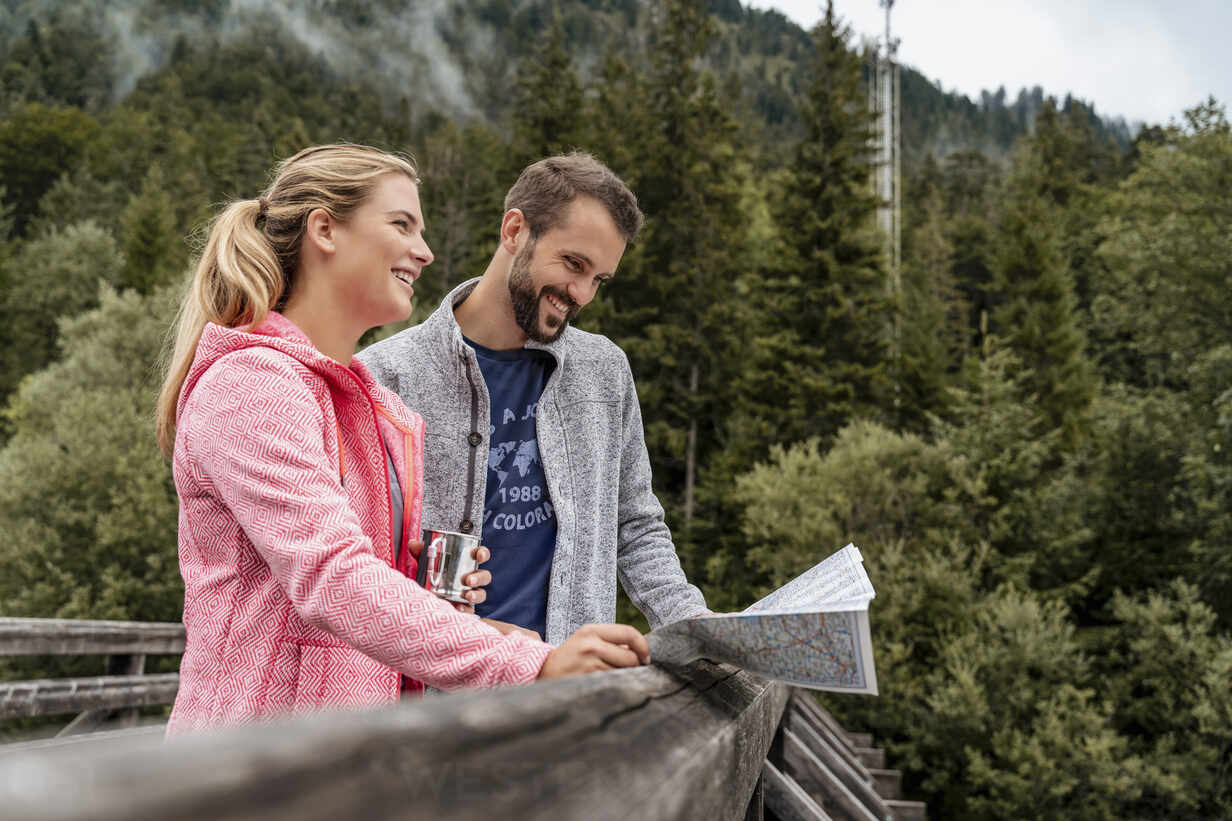 Happy young couple on a hiking trip reading map on wooden bridge, Vorderriss, Bavaria, Germany - DIGF08364 - Daniel Ingold/Westend61