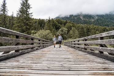 Young couple on a hiking trip walking on wooden bridge, Vorderriss, Bavaria, Germany - DIGF08367
