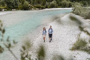 Young couple on a hiking trip walking at the riverside, Vorderriss, Bavaria, Germany - DIGF08373