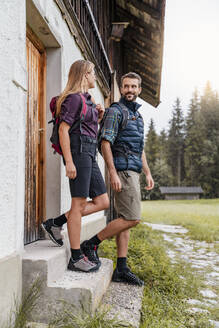 Young couple at a farmhouse during a hiking trip, Vorderriss, Bavaria, Germany - DIGF08376