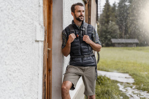 Young man at a farmhouse during a hiking trip, Vorderriss, Bavaria, Germany - DIGF08379