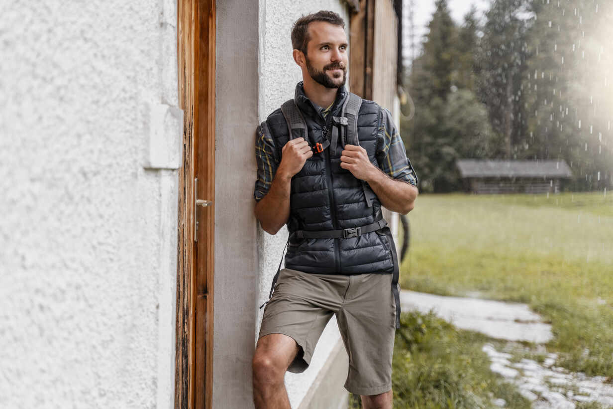 Young man at a farmhouse during a hiking trip, Vorderriss, Bavaria, Germany - DIGF08379 - Daniel Ingold/Westend61