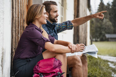 Young couple with map at a farmhouse during a hiking trip, Vorderriss, Bavaria, Germany - DIGF08382