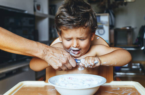 Little boy eating yogurt at home, hand of woman on the spoon - JCMF00185