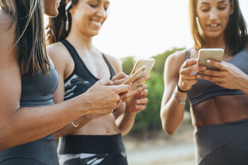 Three sportswomen using smartphones after workout - JCMF00206