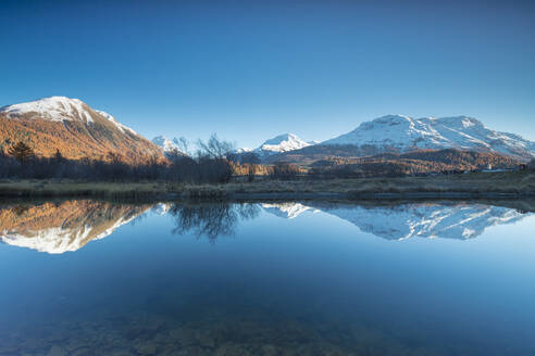 The snowy peaks and colorful woods reflected in Lake Champfer, St. Moritz, Canton of Graubunden, Engadine, Switzerland, Europe - RHPLF08818
