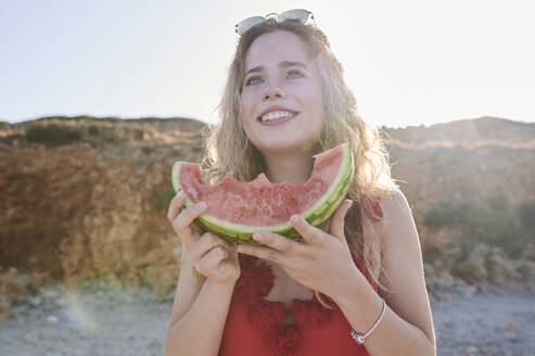 Happy young woman holding watermelon slice on the beach - IGGF01314