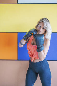 Portrait of woman with boxing gloves in gym - DLTSF00082
