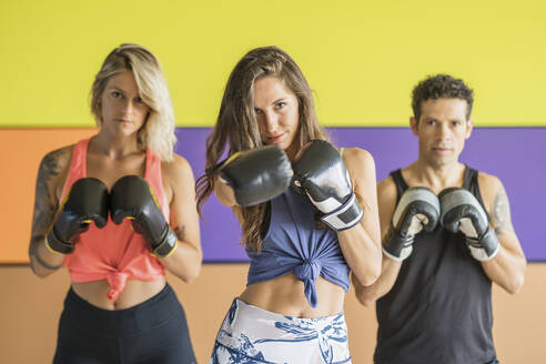 Portrait of three athletes with boxing gloves posing in gym - DLTSF00091