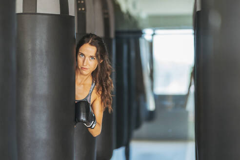 Portrait of woman with boxing gloves behind sandbag in gym - DLTSF00094