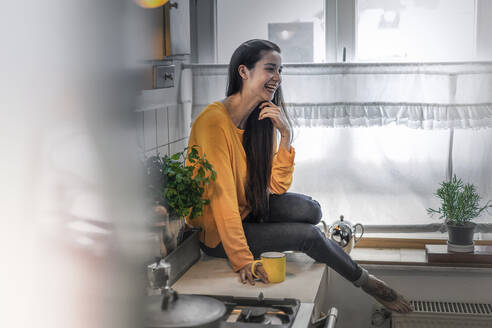 Happy young woman sitting on kitchen counter at home - RIBF00983