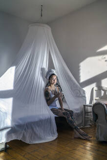 Tattooed young woman drinking glass of water in canopy bed - RIBF01007