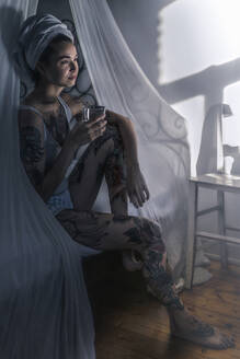 Tattooed young woman drinking glass of water in canopy bed - RIBF01010