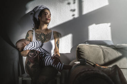 Tattooed young woman holding her baby at home enjoying the sunshine - RIBF01016