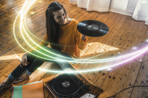 Young woman sitting on the floor at home with record and record player surrounded by a light trail - RIBF01025
