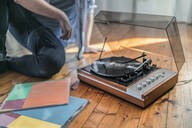 Close-up of man sitting on the floor at home with a record player - RIBF01028