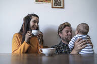 Happy family with baby sitting at wooden table at home - RIBF01043