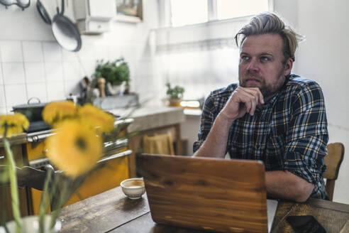 Man using laptop on kitchen table - RIBF01049