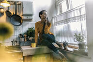 Young woman sitting on kitchen counter at home looking out of window - RIBF01058