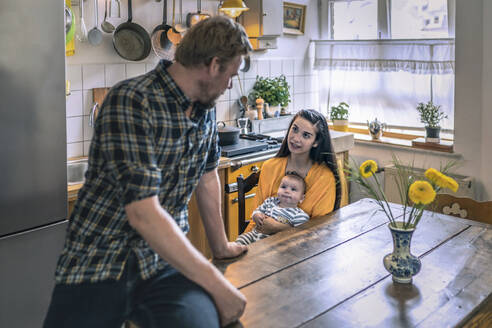 Family with baby talking in kitchen at home - RIBF01067