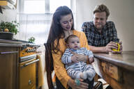 Family with baby sitting at kitchen table at home - RIBF01070