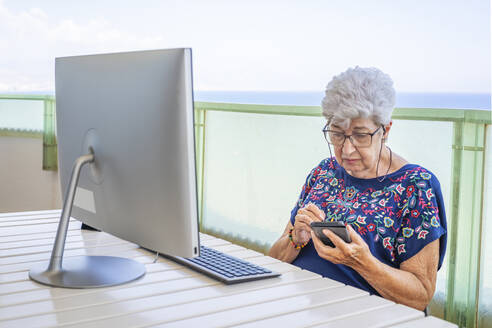 Senior woman using smartphone on the terrace - DLTSF00108