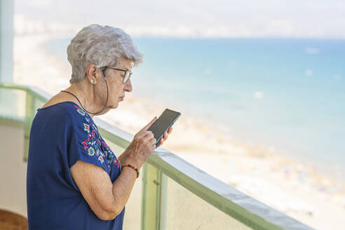 Senior woman using smartphone on a terrace - DLTSF00111