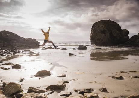 Woman jumping at the beach - UUF18970