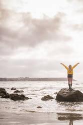 Woman wearing yellow rain jacket standing on rock - UUF18976