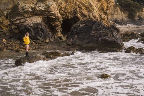 Woman wearing yellow rain jacket standing at rocky beach - UUF18979