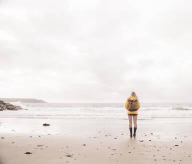 Rear view of woman wearing yellow rain jacket standing at beach - UUF18982