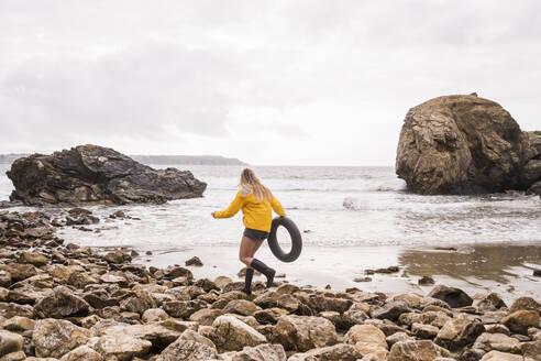 Woman wearing yellow rain jacket  with floating tire, walking aon rocky beach - UUF18988