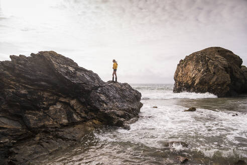 Woman wearing yellow rain jacket standing on rock at the beach - UUF18994