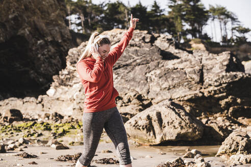 Female jogger dancing at the beach with headphones - UUF19008