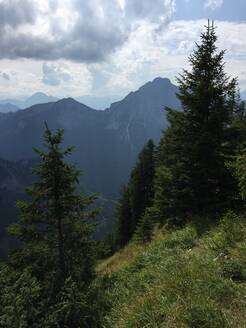 Scenic view of trees and Tegelberg against cloudy sky in Ostallgäu, Germany - JTF01319