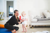 Cheerful working mother holding daughter while exercising in living room at home office - MASF13440
