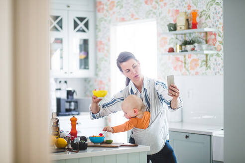 Multi-tasking mother food blogging while carrying daughter in kitchen at home - MASF13461