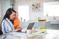 Female entrepreneur carrying loving daughter while using laptop on dining table at home office - MASF13482