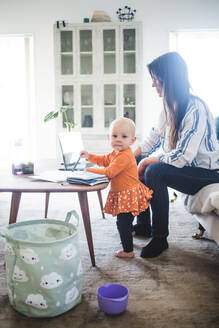 Portrait of baby girl with busy working mother in living room at home office - MASF13485