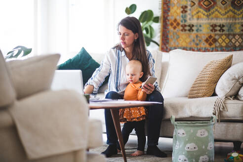 Multi-tasking mother using laptop while taking care of daughter in living room - MASF13491