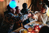High angle view of happy male and friends toasting beer bottles in log cabin - MASF13575