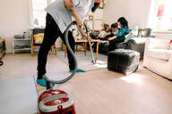 Man cleaning floor with vacuum cleaner while family sitting on sofa - MASF13725