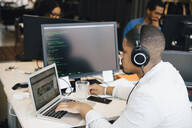 Side view of male programmer with headphones coding over laptop on desk while sitting in office - MASF13836