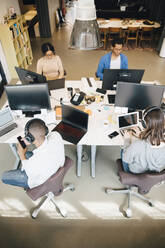 High angle view of male and female programmers using technology on desk while sitting in office - MASF13839